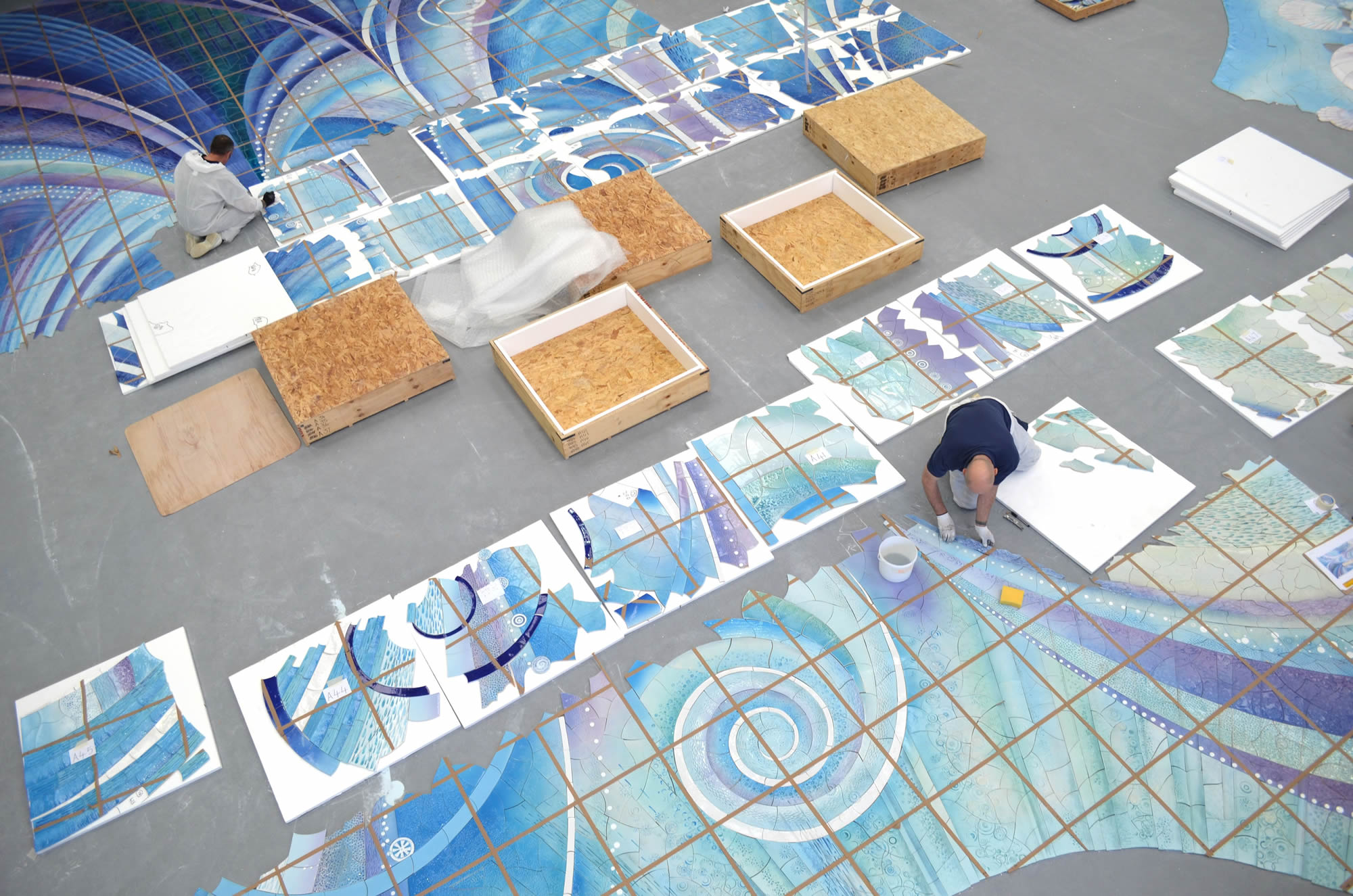 This is as much part of the 'art' of successfully producing large ceramic murals as the clay work and the glazing. Tiles are packed in a well-planned and logical manner to allow installation to commence wherever site conditions determine. Measurements, reference grid lines, full-sized plastic templates (useful for positioning and checking sizes before commencing), factory photographs and comprehensive packing details are supplied with the work.